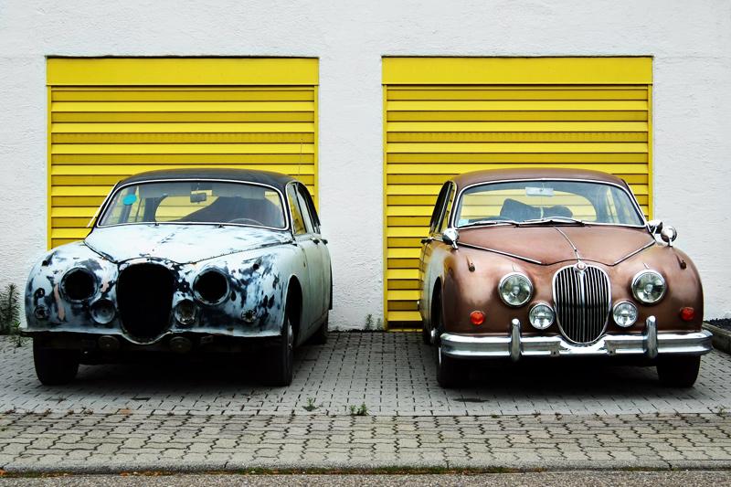 Photo de deux voitures de collection, celle de gauche une épave, celle de de droite rutilante