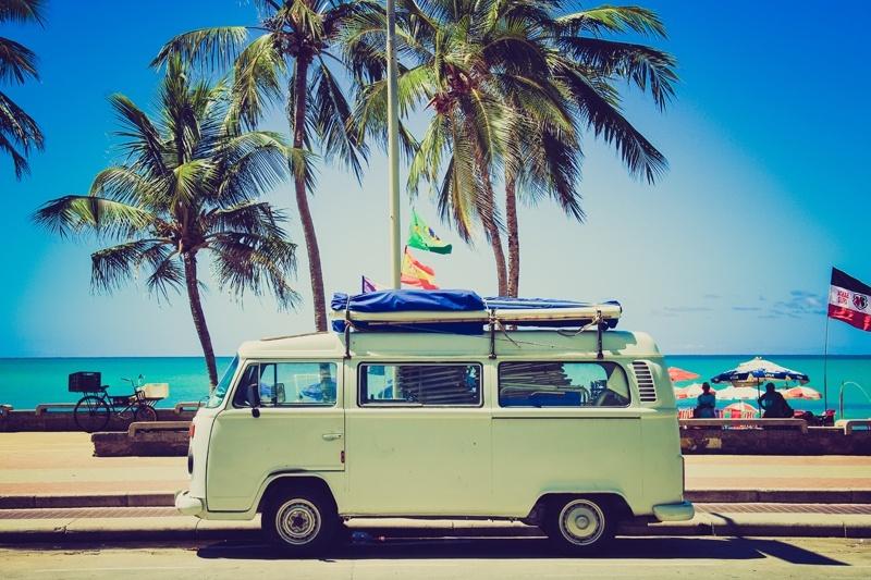 Photo d'un combi volkswagen assez vieux garé en bord de plage